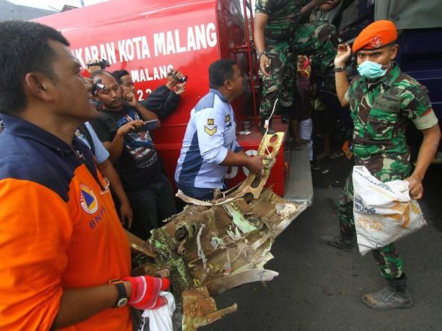 Equipes de resgate carregam uma parte do avião indonésio da Força Aérea na Indonésia, nesta quarta-feira (10). (Foto: AP)