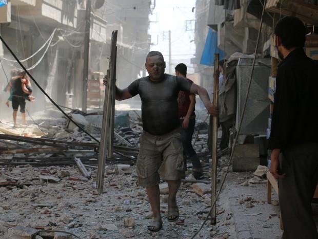 Homem carrega peças de metal nesta segunda-feira (16) em rua com escombros após ataque em Sakhur, bairro de rebeldes sírios na cidade de Aleppo (Foto: AMEER ALHALBI / AFP)