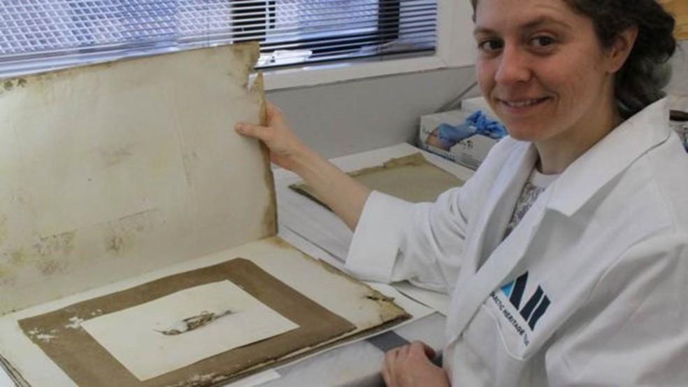 Josefin Bergmark-Jimenez mostra a pintura, que estava numa pilha de papéis coberta de mofo e fezes de pinguins (Foto: The Antarctic Heritage Trust)