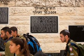 Soldados israelenses passam em frente a memorial com nome de vítimas de terrorismo em Herzl, em Israel. Nome do palestino Mohammed Abu Khdeir, morto em julho do ano passado, foi retirado da homenagem (Foto: Menahem Kahana/AFP)