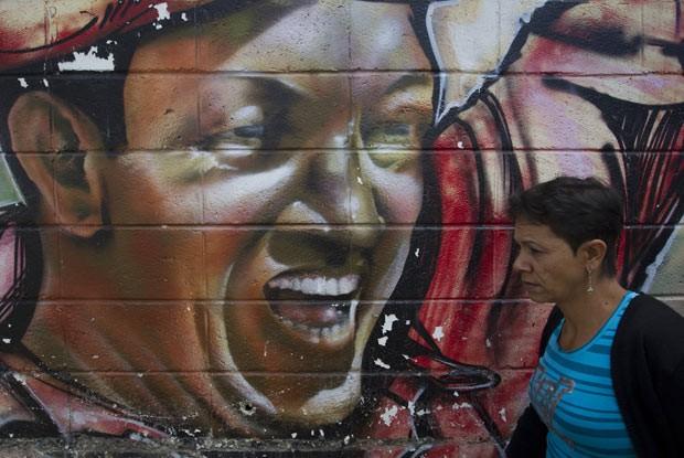 Mulher passa por mural representando o presidente venezuelano Hugo Chávez, nesta quarta-feira (9), em Caracas (Foto: AFP)