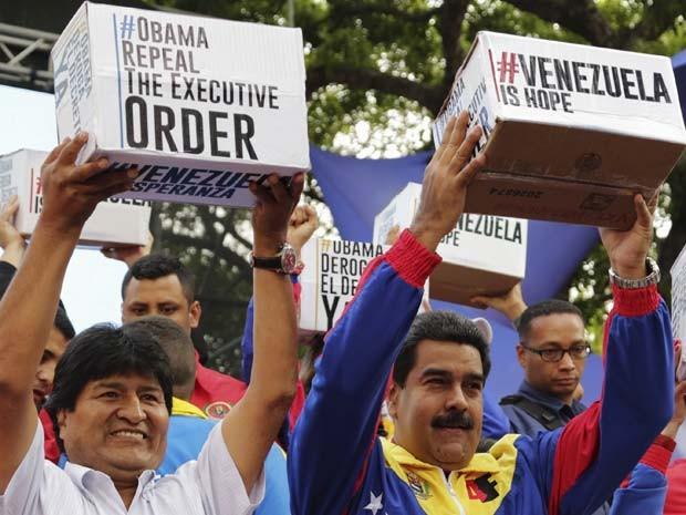 Evo Morales, presidente da Bolívia, e Nicolás Maduro, da Venezuela, exibem caixas com assinaturas para que Obama retire sanções a funcionários venezuelanos (Foto: REUTERS/Marco Bello)