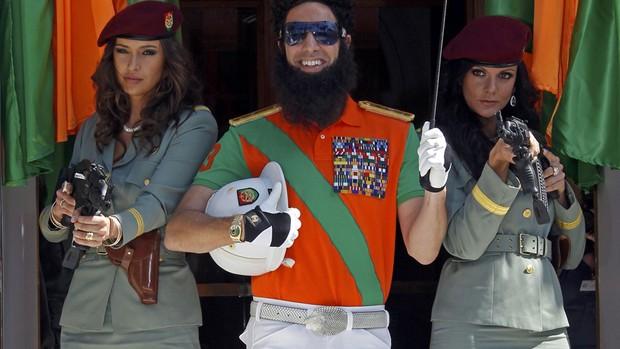 Ao lado de guarda-costas femininas, Sacha Baron Cohen sorri vestido de ditador em chegada ao Festival de Cannes (Foto: Jean-Paul Pelissier/Reuters)