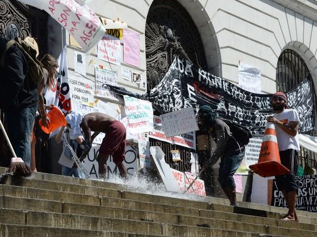 Manifestantes lavam escadaria antes de desocupar a Câmara de Vereadores nesta quarta-feira (21) (Foto: Vanderlei Almeida/AFP)