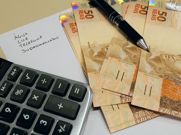 Cédulas de real e uma calculadora ao lado de contas. notas, dinheiro, reais, cotação, câmbio, valor, economia, crise, pobreza. -HN- (Foto: Marcos Santos/USP Imagens)
