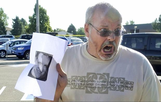 Tom Sullivan chega ao local onde as testemunhas estão sendo ouvidas em Aurora exibindo uma fotografia impressa de seu filho, Alex. (Foto: Evan Semin/Reuters)