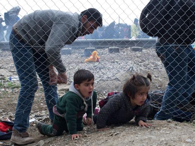 Homem ajuda crianças a passar sob cerca na fronteira da Grécia com a Macedônia nesta segunda-feira (29) (Foto: Petros Giannakouris/AP)