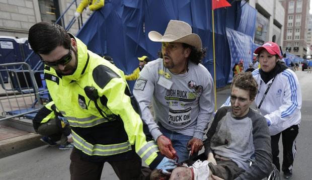 Arredondo auxilia no resgate de Jeff Bauman após perder parte das duas pernas nas explosões em Boston. Na imagem, o ativista segura com a mão direita uma das artérias da vítima, para estancar o sangramento (Foto: Charles Krupa/AP)