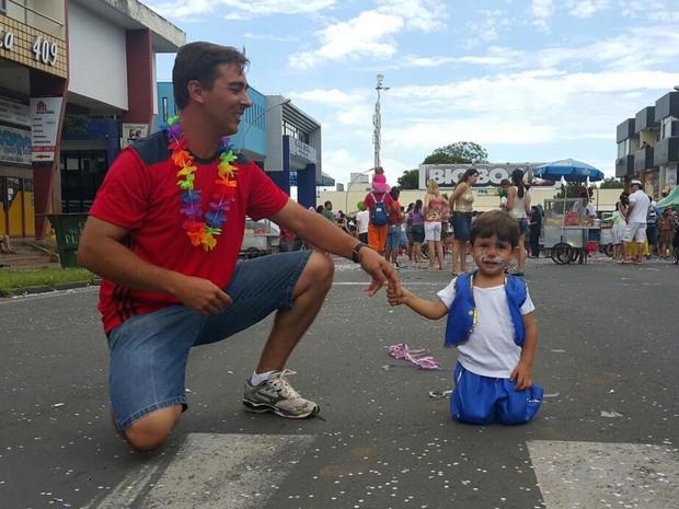 O bombeiro Leandro Reis e o filho Lorenzo, de 2 anos, durante celebração do bloco Calango Careta em Brasília (Foto: Raquel Morais/G1)