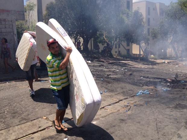 Morador  carrega colchão em meio a fumaça durante reintegração de posse (Foto: Paulo Piza/G1 )