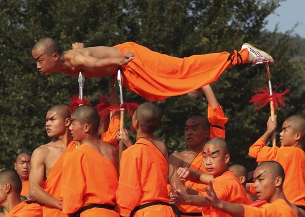 Um monge deitou sobre lâminas de lanças durante a cerimônia de abertura de um festival de artes marciais na cidade de Putian, na província de Fujian, na China. (Foto: China Daily/Reuters)