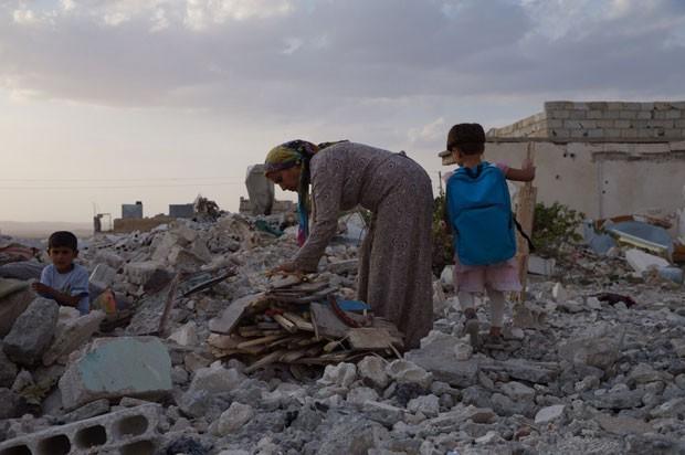 Mulher e crianças em meios aos destroços na cidade síria de Kobane; cidade foi destruída em combates com Estado Islâmico (Foto: Gabriel Chaim/G1)