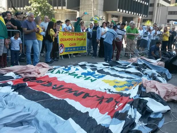 Boneco inflável com a imagem de Lula é desenrolado sob os olhares de pessoas que passeiam na Paulista (Foto: Gabriela Gonçalves/G1)