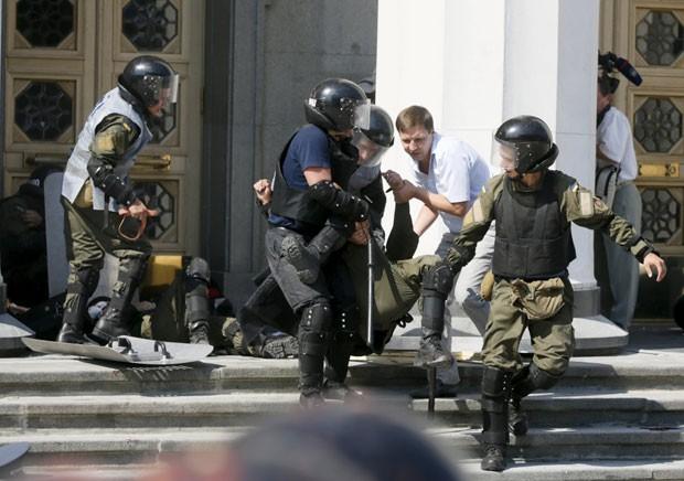 Policial ferido é carregado na frente do Parlamento ucraniano em Kiev nesta segunda-feira (31) (Foto: Valentyn Ogirenko/Reuters)