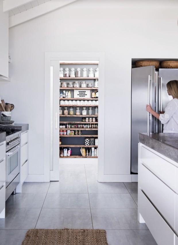 Praticidade. Além de organizar comidas e mantimentos, a despensa também ajuda a esconder alguns eletrodomésticos. O rack de temperos foi pintado em um tom escuro para dar sensação de profundidade (Foto: Chris Warnes Warnes & Walton / Living Inside)