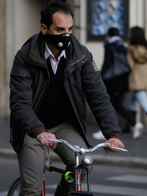 Ciclista usa máscara de proteção em Roma, em registro feito na última quinta-feira (24). (Foto: Gregorio Borgia/AP)