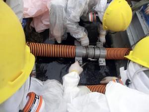 Foto divulgada pela Tepco mostra funcionários checando um cano na unidade de descontaminação de água radioativa da usina nuclear Daiichi, em Fukushima. Foto divulgada pela Tepco mostra funcionários checando um cano na unidade de descontaminação de água ra (Foto: AFP Photo/Tepco)