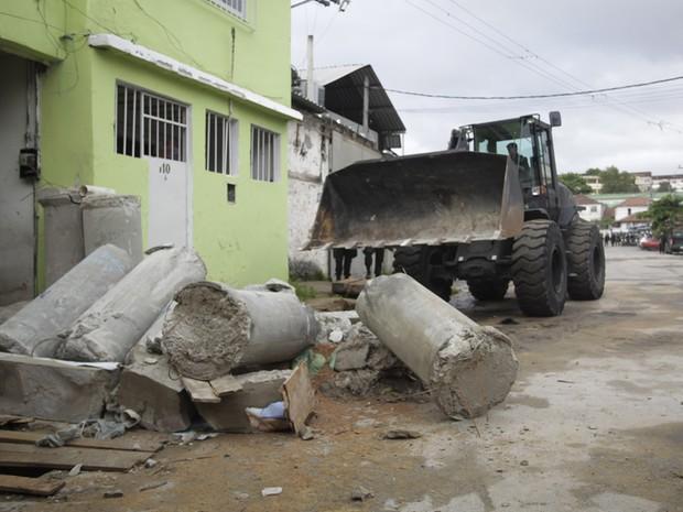 Retroescavadeira retira manilhas de rua na comunidade de Manguinhos (Foto: Ide Gomes/G1)