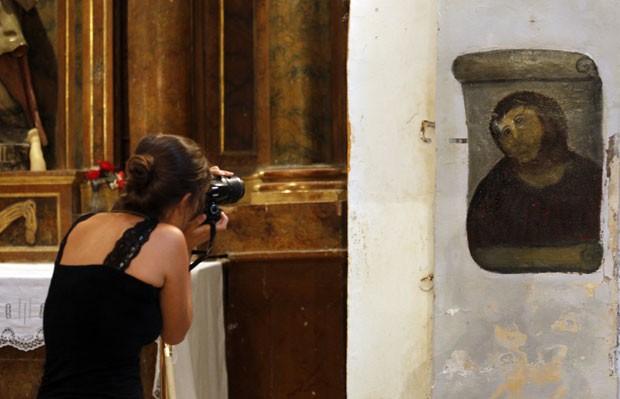 Turista fotografa obra restaurada por Cecilia Giménez em igreja na Espanha. (Foto: Censar Manso/AFP)