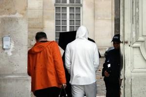 Benzema, com casaco branco, chega para depoimento na polícia em Paris (Foto: MATTHIEU ALEXANDRE / AFP)