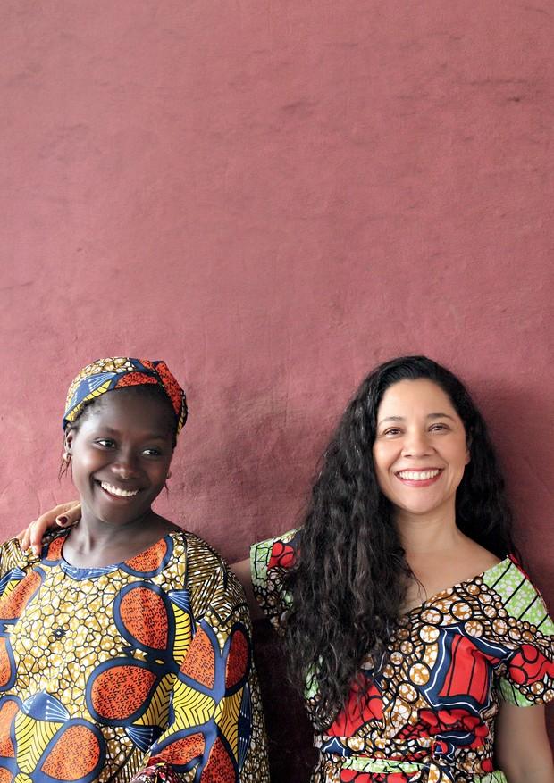 Katia, à direita, com Segunda Naçana em Guiné-Bissau. As duas usam vestidos que confeccionaram na oficina de costura montada pela brasileira no país africano (Foto: Fátima Rodrigues)