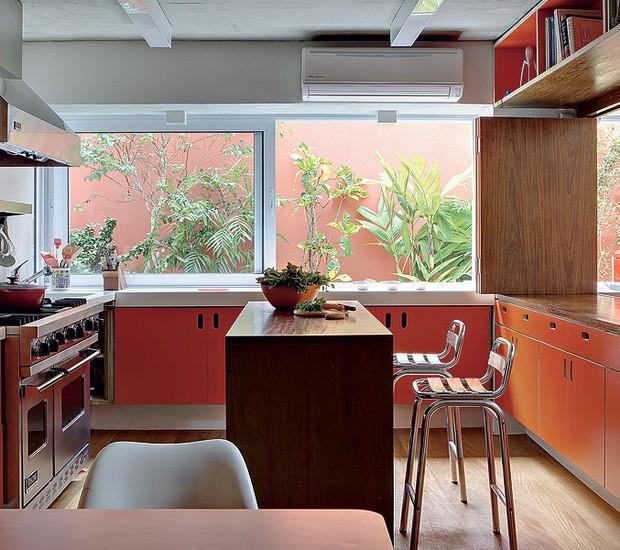 """A antiga cozinha ganhou status de espaço gourmet. Os armários foram revestidos de laminado laranja. O arquiteto André Vainer adora usar cor em seus projetos. """"O branco é muito tirânico: reflete a luminosidade e ofusca a visão"""", opina (Foto: Edu Castello/Casa e Jardim)"""