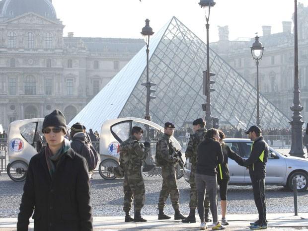 Homens armados reforçam segurança em frente ao Museu do Louvre, em Paris (Foto: Jacques Brinon/AP)