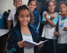 LEITURA Com os cabelos molhados da aula de surfe, Ingrid do Rosário, de 8 anos,  faz reforço  de português no  Projeto Ondas   (Foto: Guilherme Zauith/ÉPOCA)