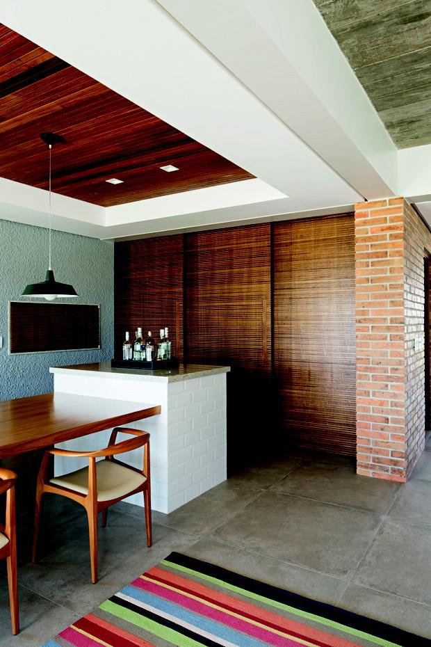 Integração | As portas de correr produzidas pela Collett Móveis, com ripas de louro freijó, unem - ou separam, conforme a necessidade - a cozinha da sala de jantar (Foto: Marcelo Sarmento)