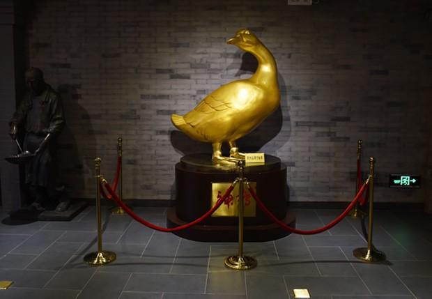 Estátua dourada de pato é vista no museu do pato laqueado em Pequim, na China (Foto: Greg Baker/AFP)
