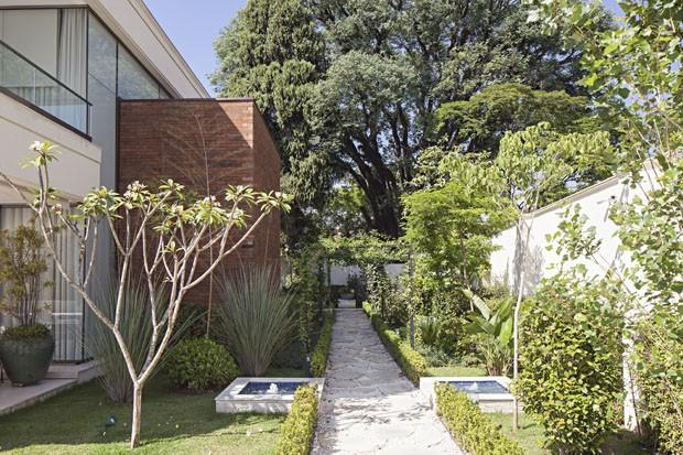 Casa é rodeada por jardim com flores, horta e caminhos delicados (Foto: Divulgação)