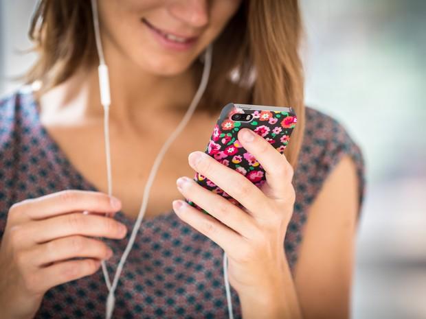 -HN- Mulher utiliza seu celular com fones de ouvido (Foto: GARO/Phanie)