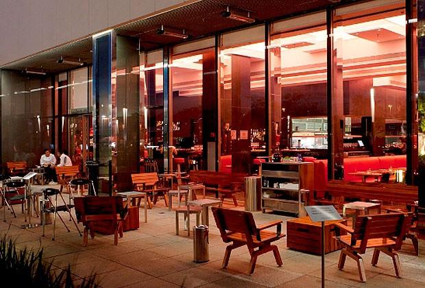 Para a área externa, o arquiteto criou as cadeiras e os bancos de madeira muiracatiara. Os painéis de vidro em toda a fachada permitem a integração com os ambientes internos   (Foto: Fernando Laszlo/Divulgação)