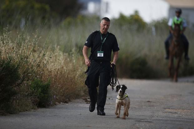 Policial da Scotland Yard usa cachorro nas buscas pela menina inglesa Madeleine McCann, que desapareceu em 2007 quando passava férias com a família no sul de Portugal, neste sábado (7) na região da Praia da Luz (Foto: Rafael Marchante/Reuters)