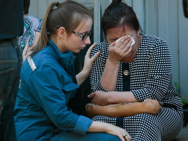 Uma funcionária do serviço de emergência consola uma mulher que perdeu colegas e parentes do Quirguistão após incêndio em armazém em Moscou, na Rússia (Foto: Ivan Sekretarev/AP)