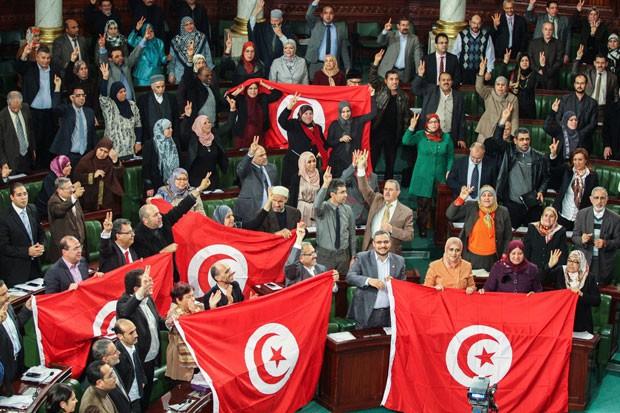 Integrantes da Assembleia Constituinte da Tunísia celebram a adoção de uma nova constituição em Túnis em foto de janeiro de 2014 (Foto: Aimen Zine/AP)