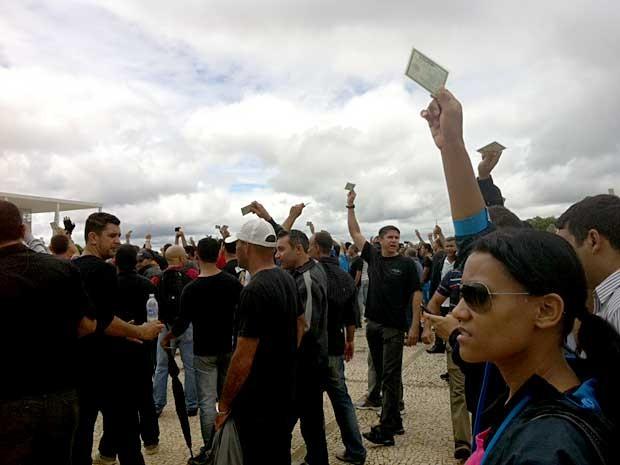 Policiais militares e bombeiros erguem as mãos com documentos durante ato contra reajuste oferecido pelo GDF (Foto: Isabella Formiga/G1)
