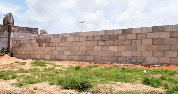Muro erguido com blocos de concreto tem quase 100 metros de extensão (Foto: Thyago Macedo/G1)