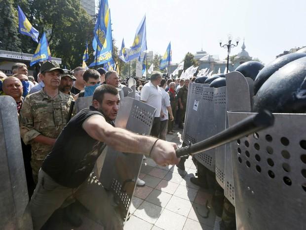 Manifestante contrário a uma reforma constitucional que concede mais autonomia ao leste separatista pró-Rússia, aprovada pelos parlamentares, bate com um cassetete no escudo de um policial durante confronto em frente ao Parlamento da Ucrânia, em Kiev (Foto: Valentyn Ogirenko/Reuters)
