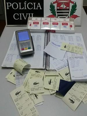 Anotações, comprovantes e máquina foram apreendidos (Foto: Polícia Civil/Divulgação)