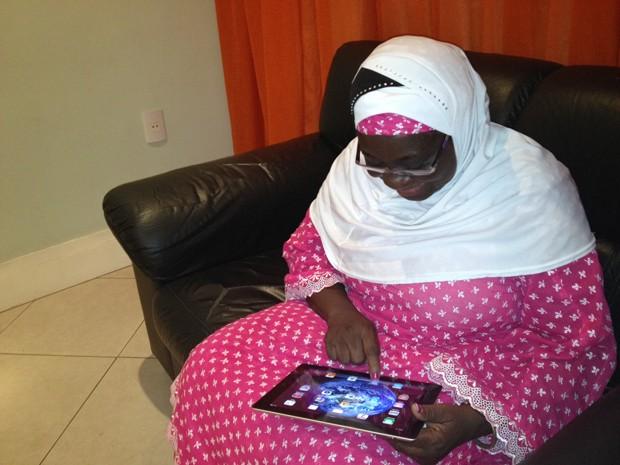 Hadijatou usa tablet para falar com a filha (Foto: Renata Soares/G1)