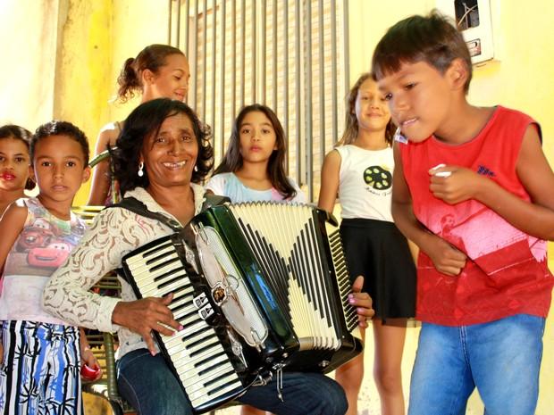 Sertaneja puxa o fole e se diverte com os netos  (Foto: Gustavo Almeida/G1)