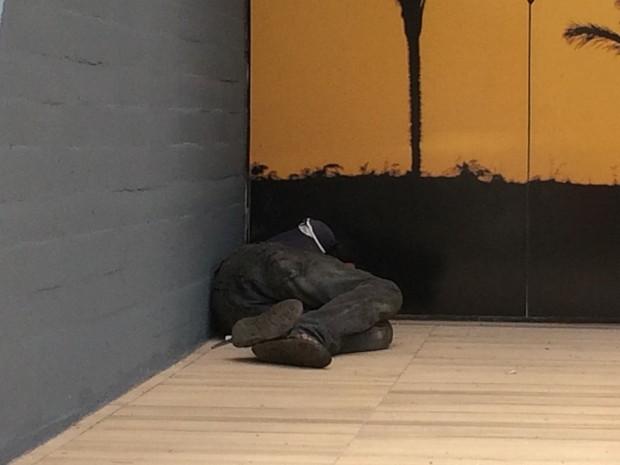 Morador de rua dorme embaixo de marquise de banco na Avenida Goiás, em Goiânia (Foto: Fernanda Borges/G1)