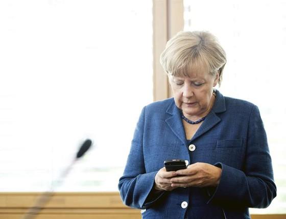 A chanceler da Alemanha, Angela Merkel, aproveita os minutos antes de uma reunião com membros de seu partido, a  União Democrata-Cristã, em Berlim, para checar mensagens em seu celular (Foto: EFE/Joerg Carstensen)