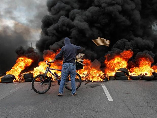 Manifestante alimenta barricada de fogo feita para bloquear pista da Marginal Pinheiros, próximo da Ponte do Socorro, na Zona Sul de São Paulo, em protesto contra o impeachment da presidente Dilma Rousseff (Foto: Marivaldo Oliveira/Código19/Estadão Conteúdo)