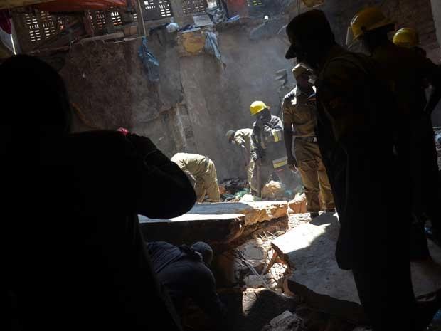 Equipes de resgate retiram escombros de um prédio que desabou nesta segunda-feira (22) em Uganda (Foto: ISAAC KASAMANI/ AFP)