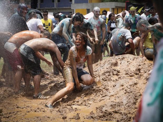 A caloura Cássia Oliveira de Lima se joga na lama durante trote na Escola Politécnica da USP (Foto: Caio Kenji/G1)