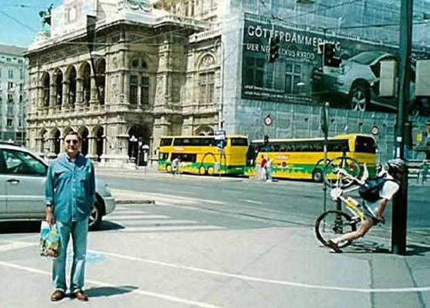Homem posava para foto, mas câmera acabou flagrando um ciclista atingindo em cheio um poste. (Foto: Reprodução/Oddee.com)