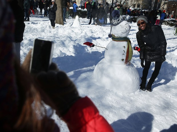 Jovem posa ao lado de boneco de neve em Dupont Circle, na capital Washington (Foto: Alex Wong/Getty Images/AFP)
