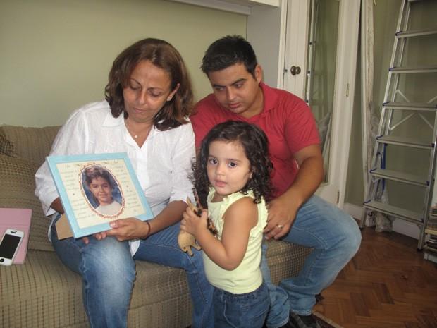 Bárbara com o filho Pedro, a neta Gabriela e a foto da filha Luisa, uma das oito vítimas (Foto: João Bandeira de Mello/G1)